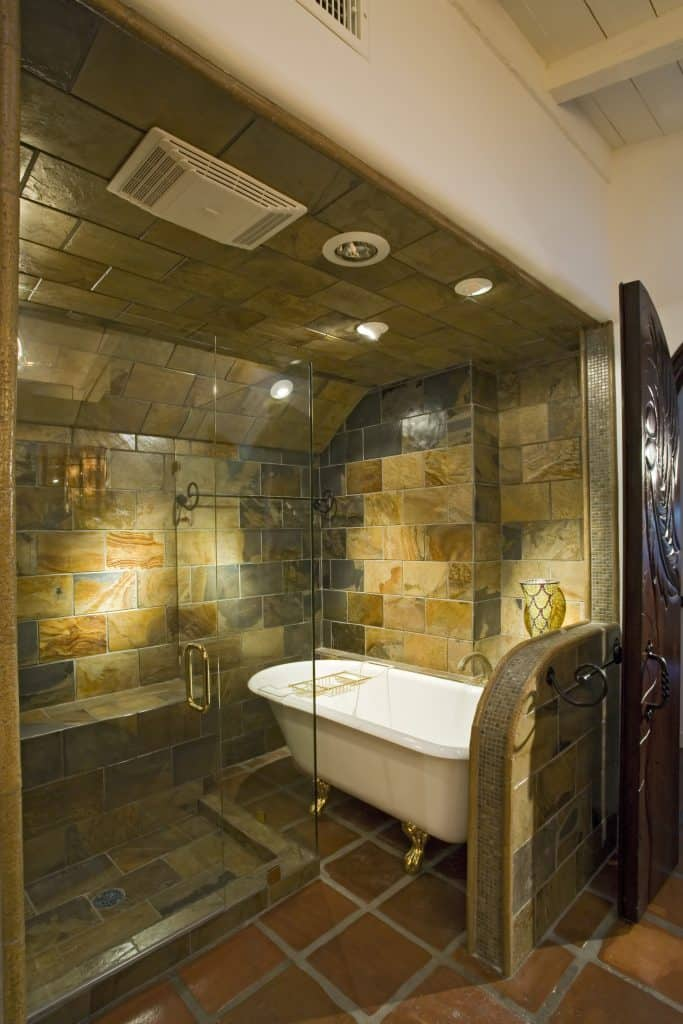 he clawfoot tub with gold accents and the dark tile bring to mind an ancient tavern or castle.