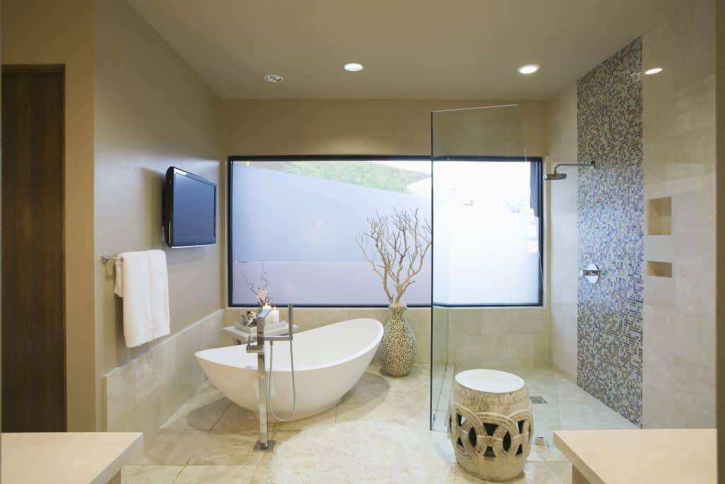 The large glass shower door in this bathroom makes it feel open and airy, while the tub gives it that relaxing, spa-like ambiance.