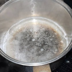 Vinegar and water boiling in burnt pot