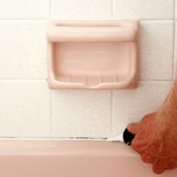 applying caulk in bathtub